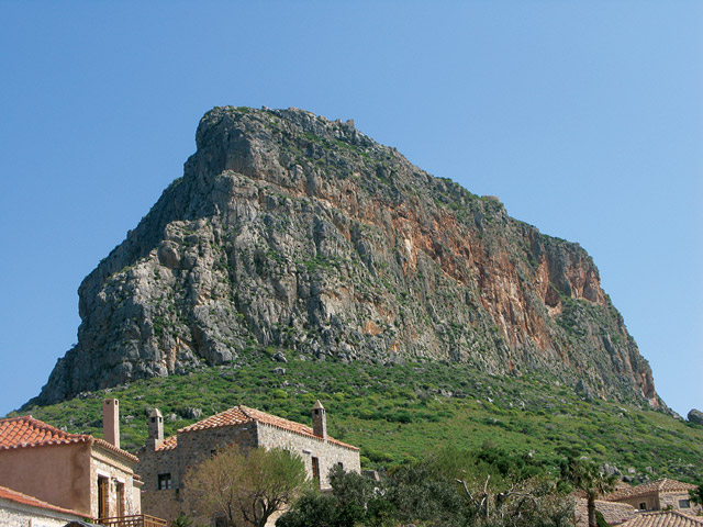 "View of the rock on which the castle and the town of Monemvasia are built. The town's name derives from two Greek words, ""mone"" and ""emvasia,"" meaning ""single entrance."""