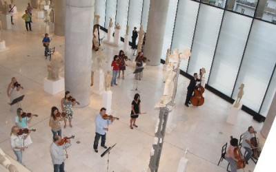 """The Orchestra of Colors playing orchestral pieces from """"Gioconda's Smile"""" (Manos Hadjidakis) - view from the terrace overlooking the New Acropolis Museum's hall of ancient sculptures."""