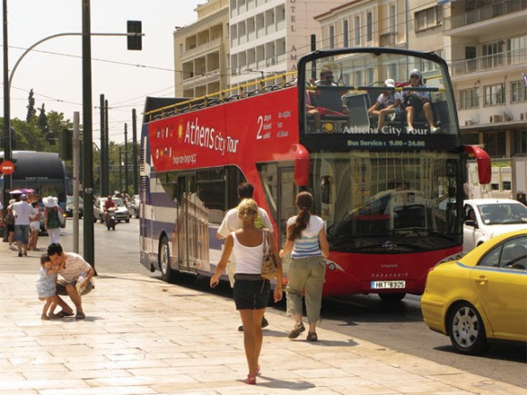 """Tourists enter a Hop On Hop Off bus for a city tour of Athens last month. Besides a heat wave, August did not present problems that would affect the stay of foreign visitors in Athens. However, this was not the case during the previous months. The latest GBR Consulting report listed obstacles that stand in the way of tourists visiting the Greek capital, such as the """"ghettoization"""" of the historic center and the non-access to archaeological sites, roads, ports and hotels due to continuous blockade operations of Greek unionists."""