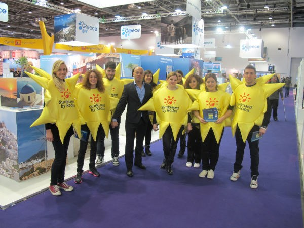 "A happy troupe of ""Sunkissers"" in the Greek segment at the 33rd World Travel Market. The ""Sunkissed by Rodos"" campaign is part of a broader promotional program of Rodos by P.RO.TOUR, the Rodos Tourism Promotion Organization."