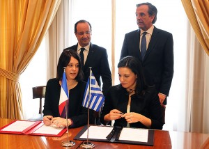 Greek Prime Minister Antonis Samaras (right) and French President Francois Hollande look on as Greek Tourism Minister Olga Kefalogianni (right) and French Minister for Trade, Commerce and Tourism Sylvia Pinel sign the Greek-French tourism agreement