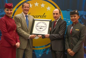 Qatar Airways Chief Executive Officer Akbar Al Baker is presented with the Skytrax 2013 Best Business Class In The World award by CNN International anchor Richard Quest, flanked by cabin crew, at the recent Paris Air Show.