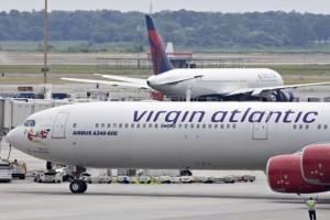 A Virgin Atlantic plane taxis past a Delta plane at John F.