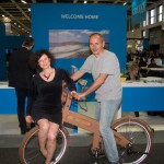 Cocomat - Paul Efmorfidis, Founder and CEO of Coco-Mat, gives Orsalia Partheni (translator-interpreter) a ride on the famous wooden Coco-Mat eco-bike.