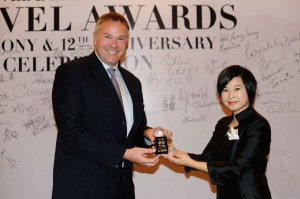 """Etihad Airways General Manager for China, Remco Althuis, accepts the award for """"Best First Class Cabin"""" from Xiao Yang, editor-in-chief of Travel & Leisure magazine, at a presentation ceremony held at the Swissotel in Beijing, China."""