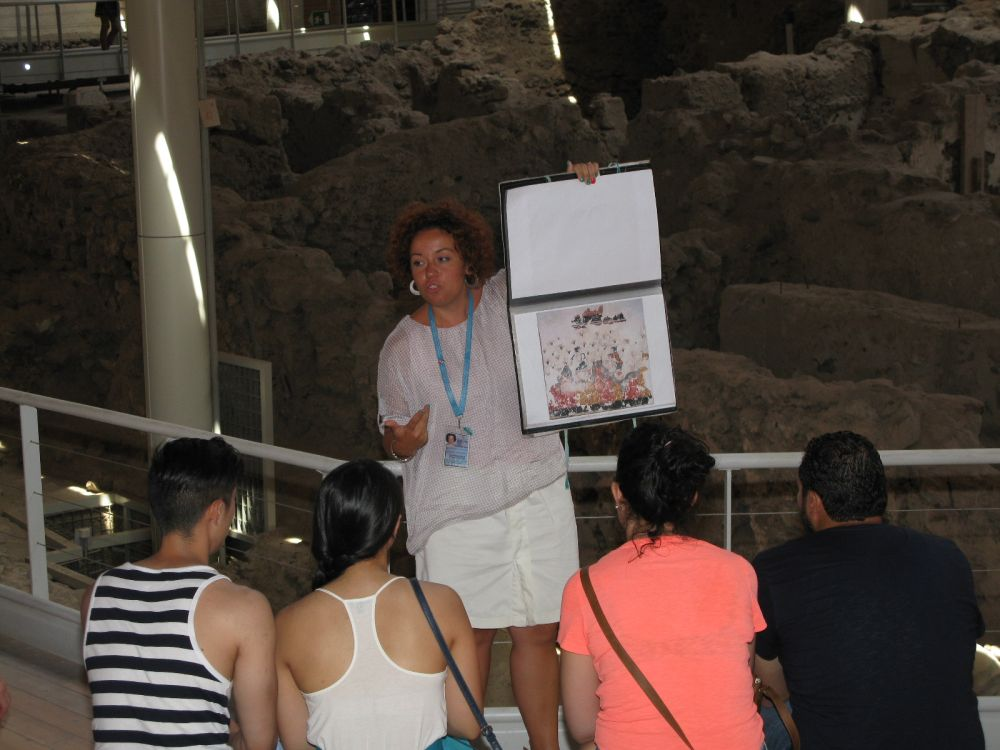 A tour guide at Akrotiri shows tourists wall-paintings that have been discovered at the site but have yet to be displayed due to lack of space at the Museum of Prehistoric Thera. Photo © GTP