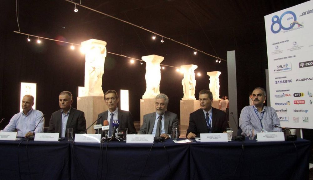 """The press conference for the 80th Thessaloniki International Trade Fair (TIF) on Thursday. Replicas of Thessaloniki's famed """"Magemenes"""" (Enchanted) can be seen in the background."""
