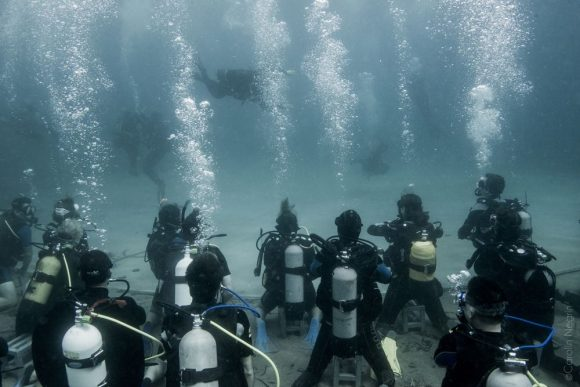 """The underwater audience observing the """"Drops of Breath"""" dancing team."""