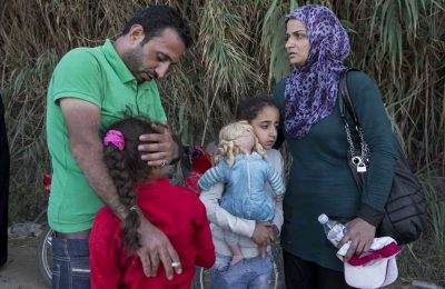 Syrian refugee parents Afeesh and Rasha hug their daughters shortly after landing on the Island of Lesvos, Greece. Photo © UNHCR/I.Prickett