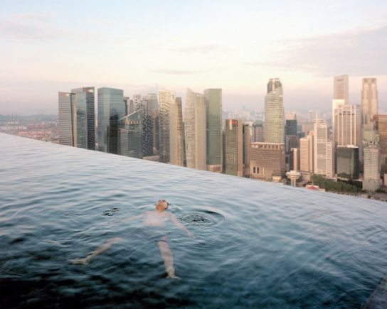A man floats in the 57th-floor swimming pool of the Marina Bay Sands Hotel, with the skyline of the Singapore financial district behind him. 2013 Paolo Woods & Gabriele Galimberti—INSTITUTE