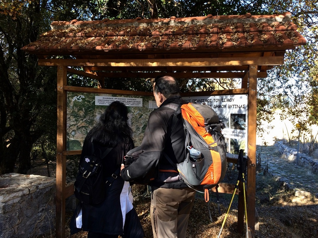 Hikers study a special map of the Menalon Trail route ahead of their trek in the Greek countryside.