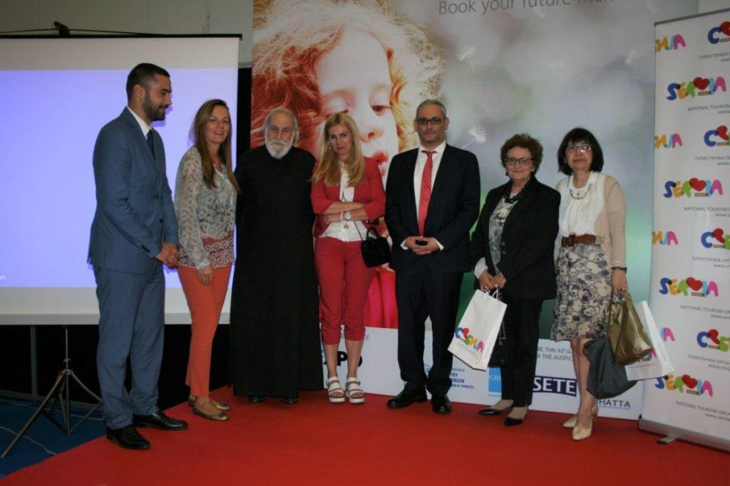 Αναμνηστική φωτογραφία. Από αριστερά προς δεξιά: ο εκπρόσωπος της Πρεσβείας της Δημοκρατίας της Σερβίας στην Ελλάδα κύριος Nemanja Dikovic, η εκπρόσωπος ΕΟΤ Σερβίας και υπεύθυνη για την Ελληνική αγορά κυρία Tamara Raskovic, ο εισηγητής π. Σταμάτης Σκλήρης, γιατρός, ζωγράφος, αγιογράφος και θεολόγος, η δεύτερη εκπρόσωπος του ΕΟΤ Σερβίας κυρία Natasa Drulovic, ο ιστορικός θεολόγος, συνιδιοκτήτης της εταιρίας Theotokis Travel Congresses και project manager του «Αγίων Συναντήσεις», κύριος Γιώργος Ν. Ιορδανίδης, η συνιδιοκτήτρια της εταιρίας Theotokis Travel Congresses κυρία Γεωργία Ιορδανίδου και η οικονομολόγος κυρία Νίκη Δημητρακοπούλου-Σκουνδρή.