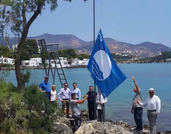 The management team of Minos Beach raises the Blue Flag.