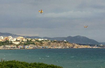Canadair fire-fighting planes diving into the port of Rafina earlier on Tuesday, as efforts continued.