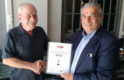 SAAE's outgoing president, Giorgos Antonaros (R), handing the Famous Brand 2018 award, recently won by the association, to new president, Dinos Frantzeskakis.