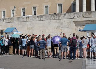 Tourists watching the Evzones at the Monument of the Unknown Soldier in front of the Hellenic Parliament, near Syntagma Square in Athens.
