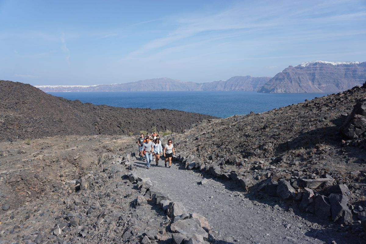 Tourists on their way to the rim of the volcanic crater on Nea Kameni. While hiking uphill there is nothing but grey and black rocks all around. The experience, however, offers a spectacular view towards Santorini's caldera. Photo © GTP