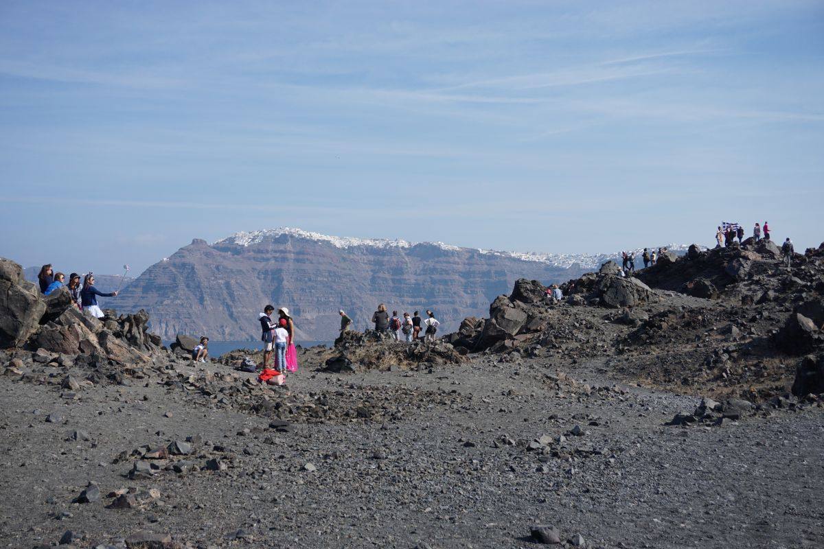 Tourists on the volcanic island of Nea Kameni with Santorini's Oia in the distance. Photo © GTP