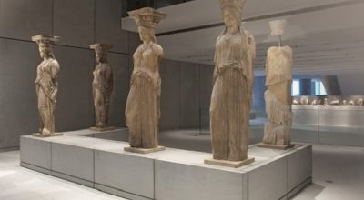 The renowned Caryatids in the Acropolis Museum. The figures were originally six but one was removed by Lord Elgin in the early 19th century and is now in the British Museum in London. The pedestal for the Caryatid removed to London (second from the left on the front) remains empty. Photo Source: Acropolis Museum