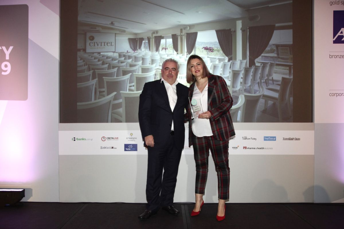 Civitel Olympic Cluster Sales Manager Angeliki Ladia receving the award from General Panhellenic Federation of Tourism Enterprises (GEPOET) Secretary General Aris Marinis.