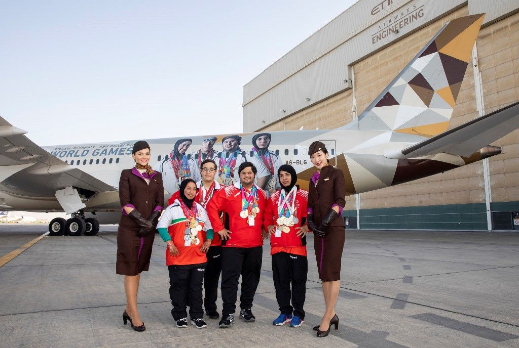 Special Olympics athletes infront of the branded Boeing 787-9 flanked by Etihad Airways cabin crew.
