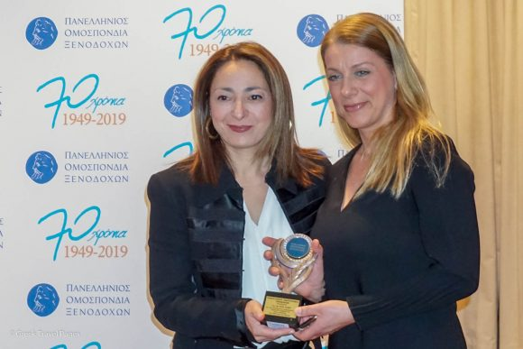 Representative of Dia Kapsi receiving the award on her behalf from Hellenic Hoteliers Federation 3rd Vice President Konstantina Svinou.