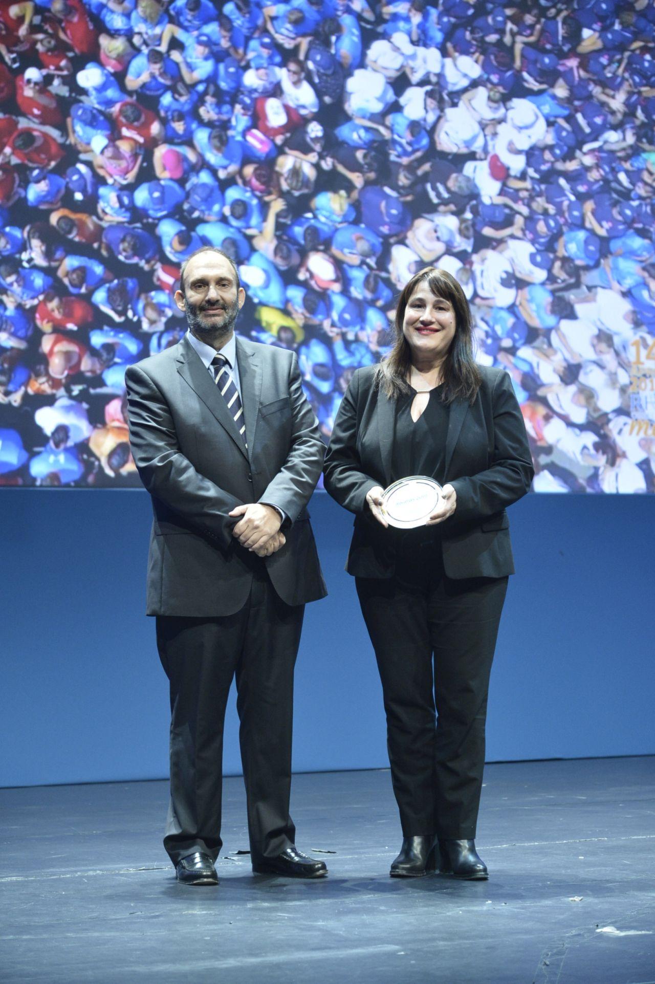 H Πρόεδρος της Οργανωτικής Επιτροπής και Αντιπεριφερειάρχης Πολιτισμού, Αθλητισμού και Παιδείας Νοτίου Αιγαίου, κ. Μαριέτα Παπαβασιλείου παραλμβάνει το βραβείο από τον κ. Πάνο Παλαιολόγο, Πρόδερο & Ιδρυτή της HotelBrain.
