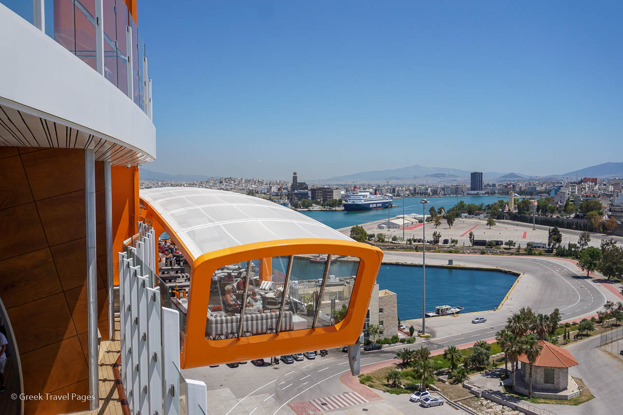 The Celebrity Edge' industry-first Magic Carpet venue - that moves up and down 16 decks to reach sea-level - overlooking Piraeus Port in Greece.