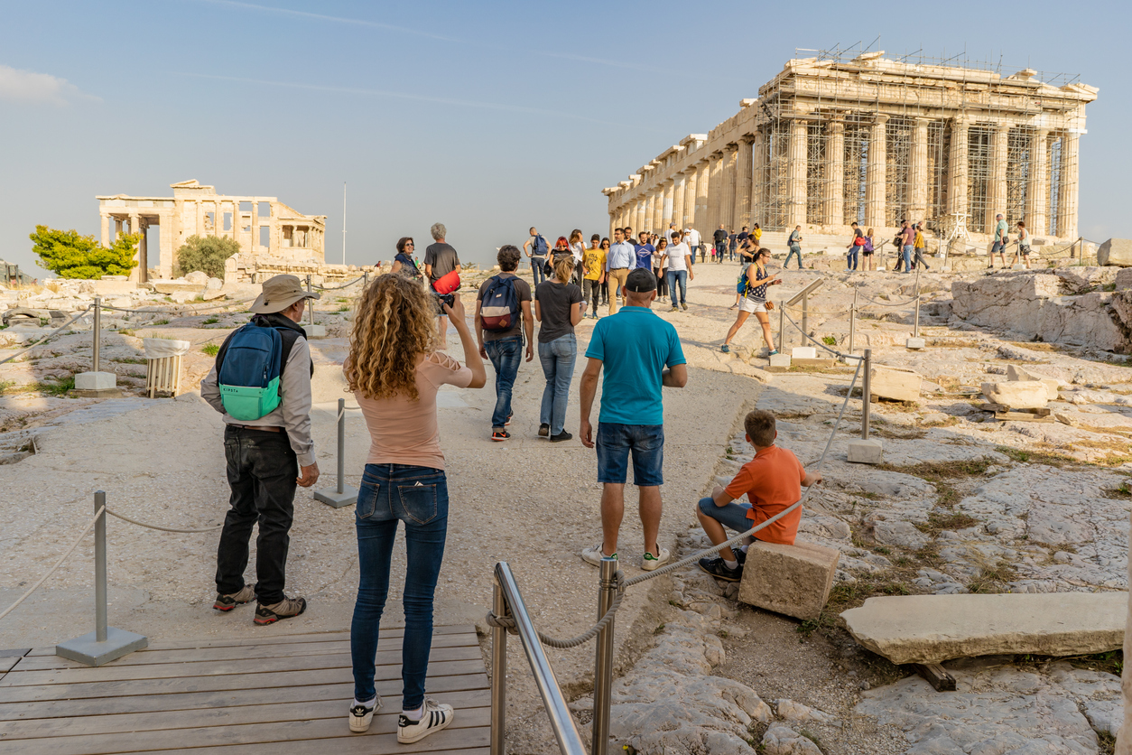Athens, Greece - October 20,2018: A stylish young woman takes a photo of the ancient Parthenon temple as she enters the famous Acropolis. Millions visit the Acropolis yearly.