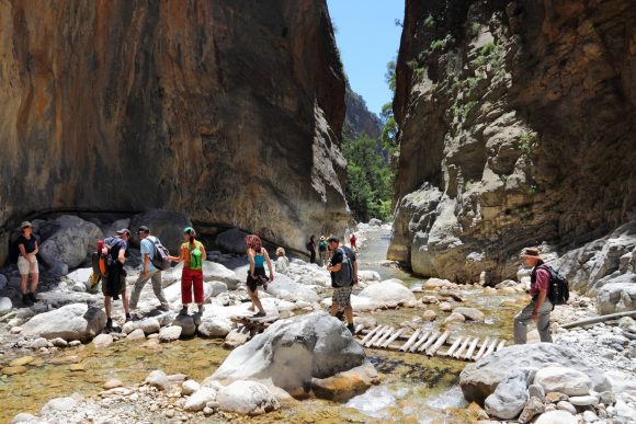 Tourists hike in Samaria Gorge in Crete, Greece. The national park is a UNESCO Biosphere Reserve since 1981.