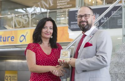 Ioanna Papadopoulou shaking hands with Alp Yavuzeser holding award