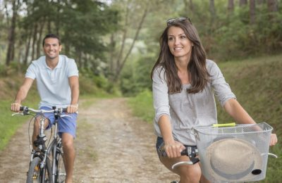 man and woman cycling in forest road