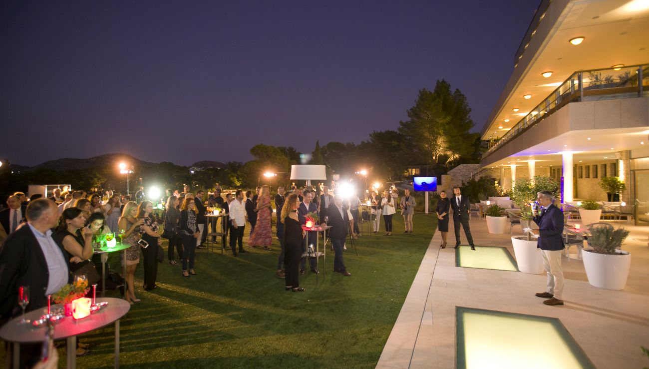 """Alitalia's George Athanassiou speaking to guests at the airline's """"Summer Winter Breeze"""" cocktail reception at the Four Seasons Astir Palace Hotel Athens."""