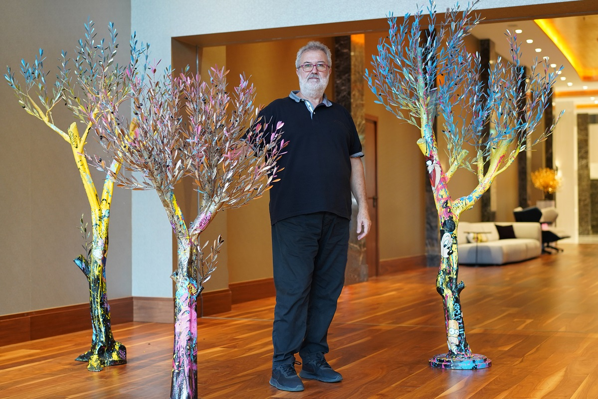 Constantinos Valaes and his artwork in the lobby of Makedonia Palace.