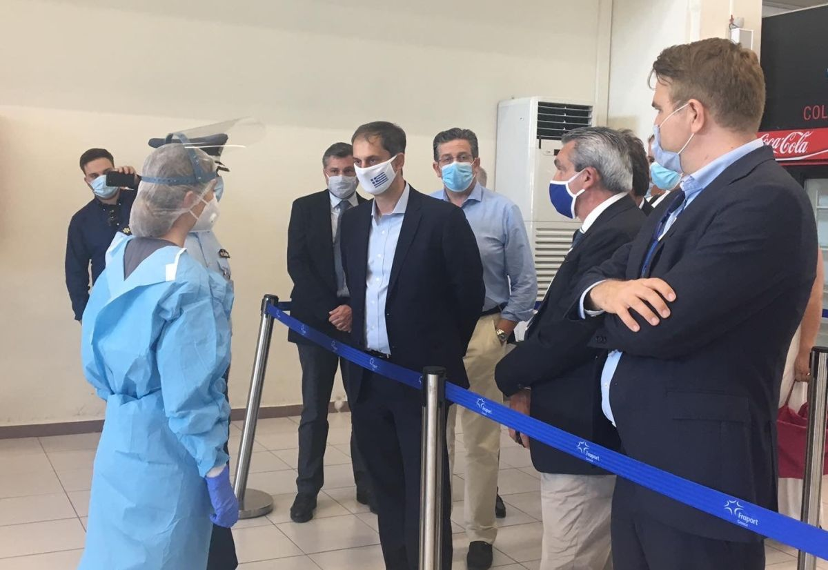 Greek Tourism Minister Harry Theoharis discussing with healthcare staff at one of Greece's regional airports.