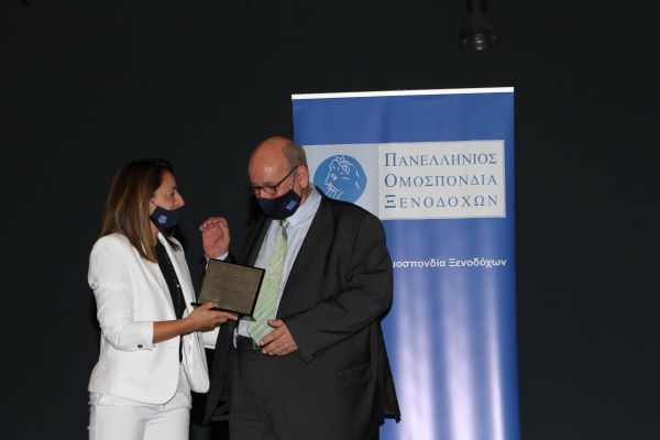 Greek hotelier Konstantinos Leventis receiving his honor from Hellenic Hoteliers Federation's 3rd VP Konstantina Svinou.