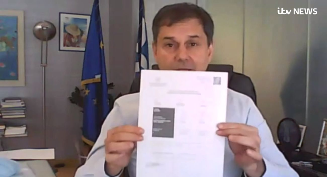 """Greek Tourism Minister Harry Theoharis holding a Greek vaccination certificate. """"It has three modes of identification: It has a QR code, a signature and a URL which you can verify,"""" he said."""