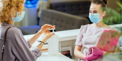 Woman Washing Hands With Alcohol Gel At Reception Counter