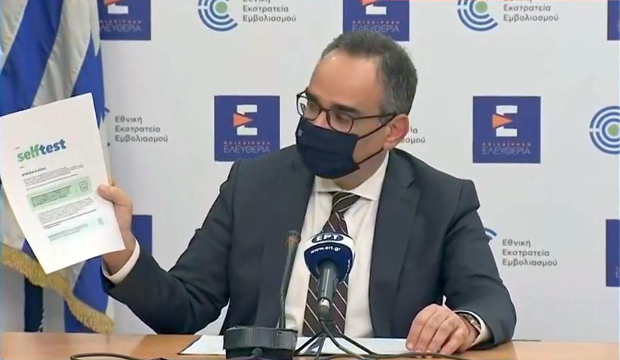 Greek Deputy Health Minister Vassilis Kontozamanis showing the self-test instructions.