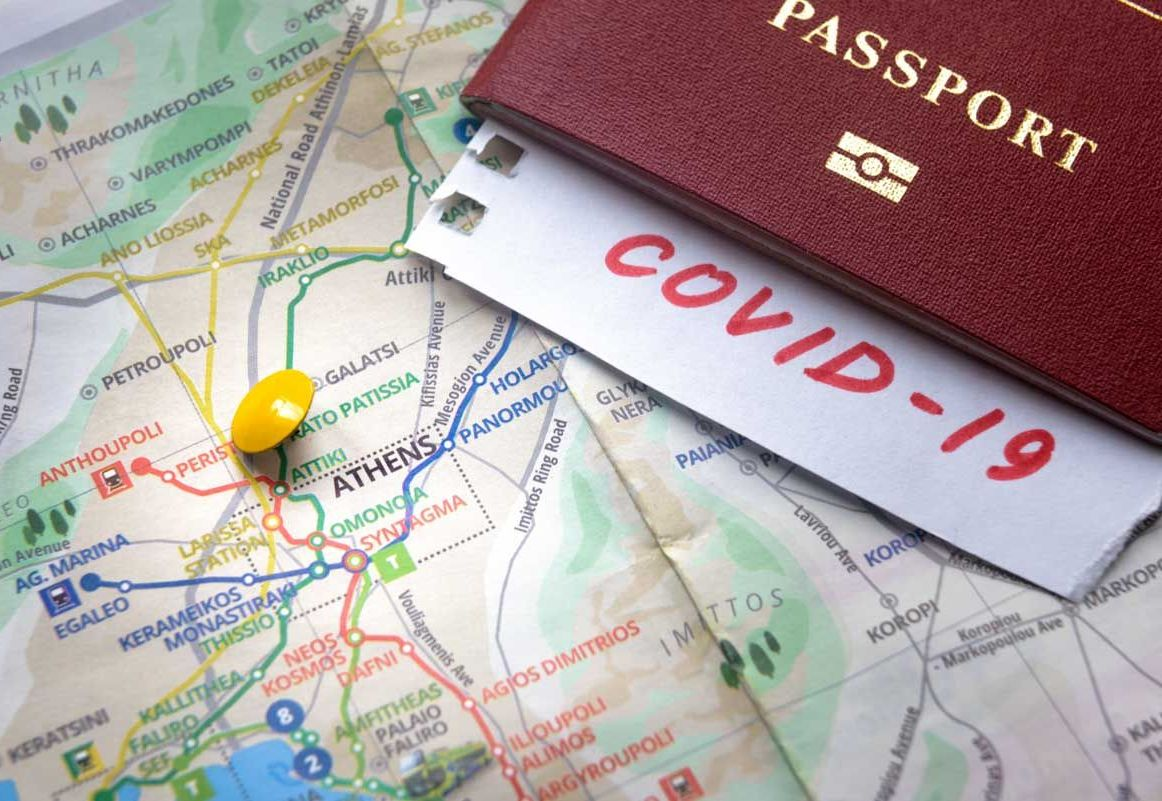 Travel and COVID-19 coronavirus in Greece, Europe. COVID mark in tourist passport on map with Athens. Tourism hit by corona virus. Medical test at border control due to coronavirus pandemic.