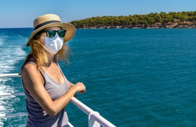 Woman standing outdoors on ferry ship with a surgical mask during Covid-19 travelling in Greece. Photo source: Shutterstock