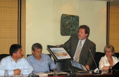 Piraeus Prefect Yiannis Michas shows the audience the prefecture's 2009 promotional campaign that flaunts the slogan
