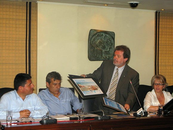 "Piraeus Prefect Yiannis Michas shows the audience the prefecture's 2009 promotional campaign that flaunts the slogan ""Turn to the Argosaronic Gulf."""