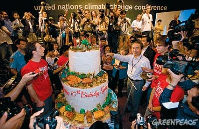 "Japanese Environment Minister Ichiro Kamoshita (right) cuts a 10th anniversary birthday cake initiated by the youth group ""Greenpeace-Solar Generation"" at the UN Climate Change Conference in Bali."