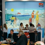 Hellenic Seaways Chief Commercial Officer Vassilis Karsaris (center of table) talks to visitors. The painting created by artist Stavros Pehlivanides especially for Hellenic Seaways is the backdrop to the stand.