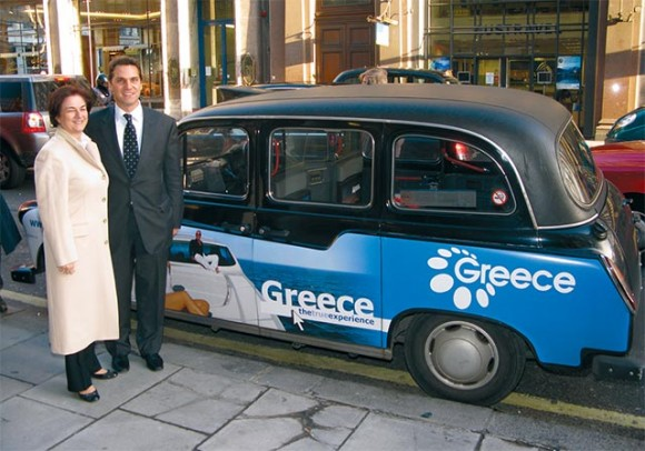 Sofia Vasiliou, GNTO's general director of promotion; and Makis Peppas, GNTO director for the U.K. & Ireland, next to a taxi cab in London parked outside GNTO London offices. The cab displays part of the organization's advertising campaign in an effort to attract British visitors to Greece.