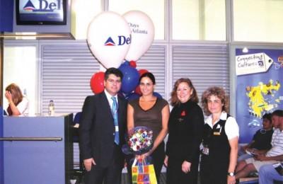 Dimitris Karagioules, Delta's commercial director with Paraskevi Sideri, the winner, a crew-member, and Voula Gravani, ACS Supervisor for Delta at Eleftherios Venizelos.