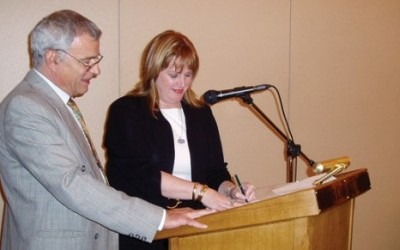 Tassos Pappas, president of the Greek chapter, with Brenda Anderson, CEO of SITE International, as she signs the founding document.
