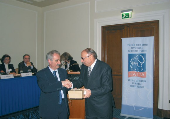 Hellenic Association of Travel & Tourism Agents' president, Yiannis Evangelou, hands over a special honor award to Dimitrios Pithis of Argo Travel for his decades of service to the Greek tourism sector. Argo Travel was first founded in 1953.